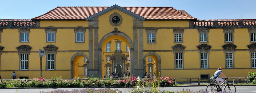 Aufnahme des Hauptgebäudes und des Uhrenflügels von der gegenüberliegenden Straßenseite. Portal und Torbogen mit Uhr sind zu sehen. Die Tür zum Schloss ist geöffnet, vor dem Eingang befinden sich mehrere Personen. Gebäude 11 und Gebäude 14. Uhrenflügel Total.