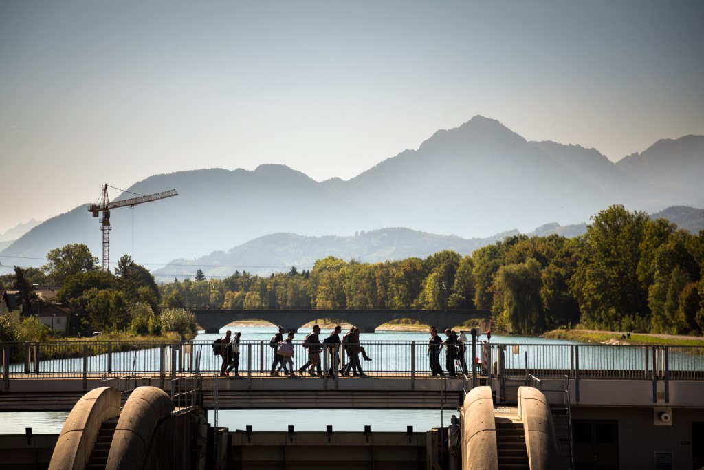 Germany, Freilassing, Bavaria, October 01, 2015, Refugees crossing the bridge from Salzburg to Freilassing in Germany. Police await them. Groups of roughly 10-30 refugees are allowed to cross every hour. Germany has reintroduced border controls with EU neighbors to try and regulate the flow of people moving across their borders. At least 800,000 refugees are expected to arrive in Germany this year. During our two-day visit to a rural southeast border crossing of Austria and Germany, up to 2,000 refugees were estimated to have crossed into Germany by rail or foot.